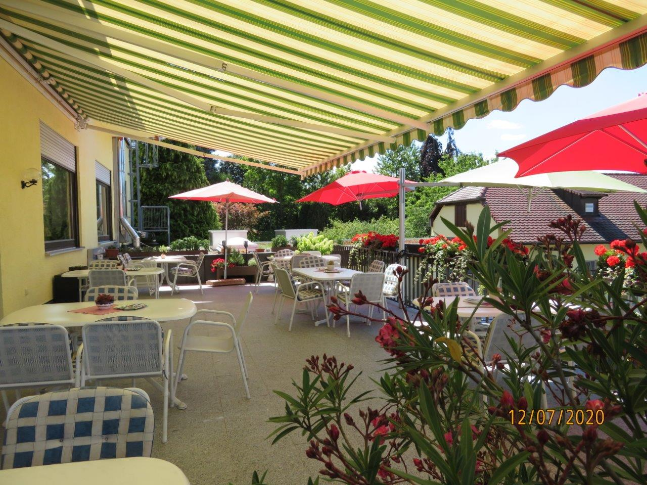 Blick auf Terrasse des Hotel Restaurant Krone mit geöffneter, grün gelb gestreifter Markise, roten Sonnenschirmen und  6 Tischen mit jeweils 6 Sitzplätzen