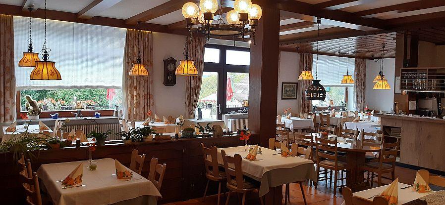Blick auf Räumlichkeiten des Hotel Restaurant Krone mit sicherem Abstand der Tische, atmosphärischer Beleuchtung und angenehmem Gesamtambiente.12 sichtbare Tische mit 2 bis 6 Personen und große runde Tafel.